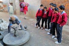 BHAKTAPUR, NEPAL - 30 DICEMBRE 2014: Gli scolari che guardano un vasaio sul lavoro in una strada affollata vicino ai vasai quadra Immagini Stock Libere da Diritti