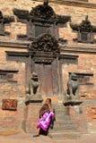 BHAKTAPUR, NEPAL - 30 DICEMBRE 2014: Una donna nepalese che si siede davanti ad una casa tradizionale Fotografia Stock Libera da Diritti