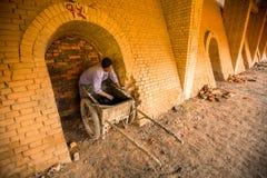 BHAKTAPUR, NEPAL - la gente local trabaja en la fábrica del ladrillo Foto de archivo libre de regalías