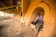 BHAKTAPUR, NEPAL - la gente local trabaja en la fábrica del ladrillo Fotos de archivo libres de regalías