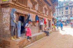 BHAKTAPUR NEPAL, LISTOPAD, - 04, 2017: Niezidentyfikowani ludzie w plenerowym podczas gdy stary człowiek czyta gazetę przy ulicą Zdjęcia Royalty Free