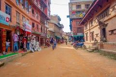 BHAKTAPUR NEPAL, LISTOPAD, - 04, 2017: Niezidentyfikowany rodzinny odprowadzenie w placu otaczaniu starzy i nieociosani budynki Fotografia Royalty Free