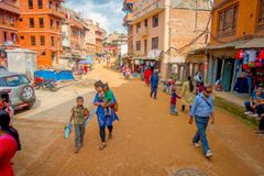 BHAKTAPUR NEPAL, LISTOPAD, - 04, 2017: Niezidentyfikowany rodzinny odprowadzenie w placu otaczaniu starzy i nieociosani budynki Zdjęcia Royalty Free