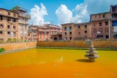 BHAKTAPUR NEPAL, LISTOPAD, - 04, 2017: Zakończenie up tradycyjna miastowa scena z sztucznym stawem kolor żółty woda przy Zdjęcie Royalty Free