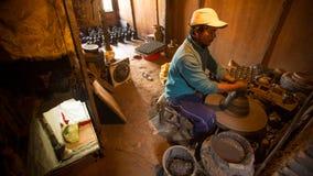 BHAKTAPUR, NEPAL - Nepalese mens die in de zijn aardewerkworkshop werken Stock Afbeelding