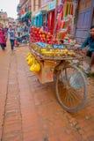 BHAKTAPUR NEPAL - NOVEMBER 04, 2017: Den oidentifierade mannen i gatamarknad med en vagn av frukter, shoppar i plazaen Arkivfoto