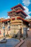 BHAKTAPUR NEPAL - NOVEMBER 04, 2017: Det oidentifierade folket som går i forntida hinduisk tempel i Durbaren, kvadrerar in Arkivfoto