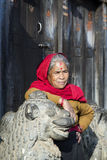 BHAKTAPUR, NEPAL � NOVEMBER 21: Nepalese woman rests on a statue Royalty Free Stock Photography