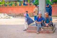 BHAKTAPUR NEPAL - NOVEMBER 04, 2017: Oidentifierat folk på det fria som in sitter i skriva in av den forntida hinduiska templet Fotografering för Bildbyråer