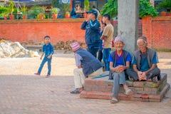BHAKTAPUR NEPAL - NOVEMBER 04, 2017: Oidentifierat folk på det fria som in sitter i skriva in av den forntida hinduiska templet Royaltyfri Foto