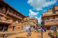 BHAKTAPUR NEPAL - NOVEMBER 04, 2017: Oidentifierat folk som plundrar en motorcykel och in går i forntida hinduisk tempel Arkivfoton