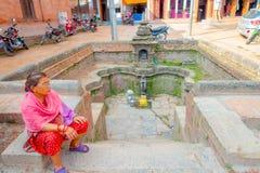 BHAKTAPUR NEPAL - NOVEMBER 04, 2017: Oidentifierat kvinnasammanträde i en plaza nästan en tom springbrunnsikt av forntida Arkivbild