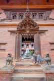 BHAKTAPUR NEPAL - NOVEMBER 04, 2017: Oidentifierat mansammanträde i skriva in av den forntida hinduiska templet i den Durbar fyrk Royaltyfri Bild