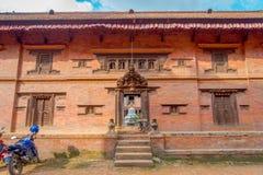 BHAKTAPUR NEPAL - NOVEMBER 04, 2017: Oidentifierat mansammanträde i skriva in av den forntida hinduiska templet i den Durbar fyrk Arkivfoton