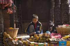 BHAKTAPUR, NEPAL - NOVEMBER 20: Portrait of unkown child selling. Goods in market in Bhaktapur on November 20, 2014 in Bhaktapur, Nepal Stock Images