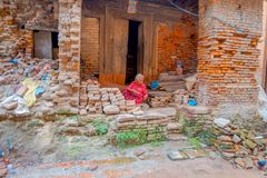 BHAKTAPUR, NEPAL - NOVEMBER 04, 2017: Unidentified old woman manipulating brick pieces, sitting in the floor, under an. Old house in the dirty and old streets Royalty Free Stock Photo