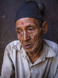 BHAKTAPUR NEPAL-OCT 14, 2012: gamala mannen sitter framme Arkivfoto