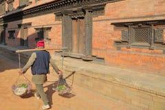 BHAKTAPUR, NEPAL: Um vegetal levando do vendedor local nas cestas no quadrado de Durbar foto de stock