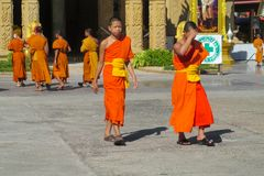 Buddhist young monks walk in the temple yard. A bhikkhu, an ordained male monastic. Buddhist monk Pali, Sanskrit bhiksu. Young Buddhist monks samanera srama royalty free stock photography