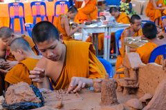 Buddhist young monks doing hand crafts in the temple yard. A bhikkhu, an ordained male monastic. Buddhist monk Pali, Sanskrit bhiksu. Young Buddhist monks royalty free stock images