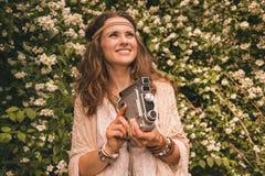 Böhmische junge Frau mit der Retro- Kamera, die oben auf Kopienraum schaut Lizenzfreies Stockbild