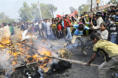 Bhopal. BHOPAL- DECEMBER 3: Violent victims hit the burning effigy during the rally to mark the 26th Year of the Bhopal Gas Tragedy in Bhopal - India on Stock Images