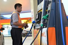 BHP Petrol Station. Petrol pump attendant holding an petrol nozzle, and checking the petrol meter Stock Images