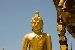 Bhudda bronsstaty med bönberlock i förgrunden Royaltyfri Foto