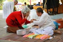 Bhuddist Nun binding a holy thread Royalty Free Stock Photo