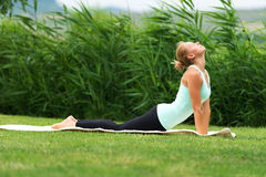 Bhujangasana cobra pose by woman on green grass in the park Royalty Free Stock Photos