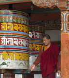 Bhutan - Buddhist Monk turning Prayer Wheels Royalty Free Stock Photography