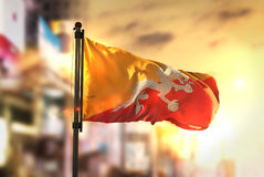 Bhutan Flag Against City Blurred Background At Sunrise Backlight. Sky royalty free stock images