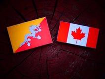Bhutan flaga z kanadyjczyk flaga na drzewnym fiszorku odizolowywającym zdjęcie stock