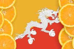 Bhutan flagga i vertikal ram för citrusfruktskivor royaltyfri foto