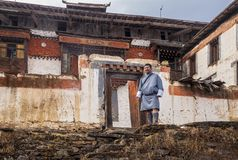 Bhutan mаn in traditional Bhutanese clothes on the background of buildings of Padjoding monas stock photography