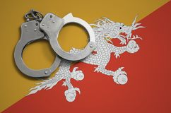 Bhutan vlag en politiehandcuffs Het concept misdaad en inbreuken in het land royalty-vrije stock foto