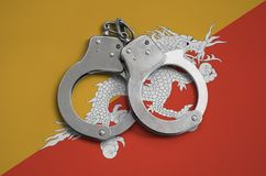 Bhutan vlag en politiehandcuffs Het concept naleving van de wet in het land en bescherming tegen misdaad stock afbeeldingen
