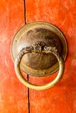 Bhutanese door knob at Drametse Goemba Dzong. Golden door knob on a red wooden door Stock Images