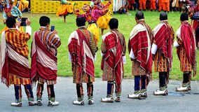 Bhutanese men in their best traditional attire witnessing a spectacular and sacred mask dance. stock photos