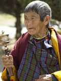 Bhutanese woman - Paro Dzong - Bhutan. An elderly Bhutanese woman with a prayer wheel at Paro Dzong (Monastery) near the town of Paro in the Kingdom of Bhutan Stock Photography