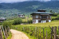 Bhutanesisk by och risfält, Ura dal, Bhutan arkivfoton