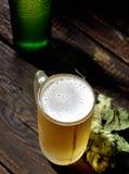 Bière écumeuse froide dans une bouteille en verre et des houblon sur un fond en bois foncé Images stock