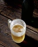 Bière écumeuse froide en verre sur un fond en bois Photo stock