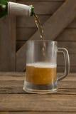 Bière étant versée dans une tasse Image stock