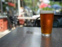 Bière ambre glacée se reposant dans un verre de pinte sur une table dehors avec l'anneau humide de tasse photographie stock libre de droits