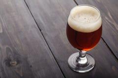 Bière anglaise rouge sur le bois foncé Photographie stock