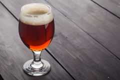 Bière anglaise rouge sur le bois foncé Image stock