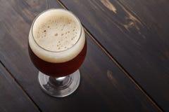 Bière anglaise rouge sur le bois foncé Image libre de droits