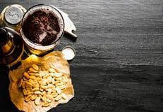 Bière avec des arachides sur la table en bois noire L'espace libre pour le texte Photos stock