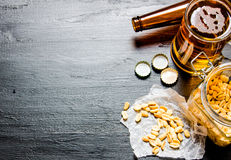 Bière avec des arachides sur la table en bois noire L'espace libre pour le texte Photographie stock libre de droits